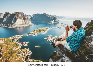 Man tourist using smartphone on cliff Travel lifestyle concept adventure outdoor in Norway Reinebringen mountains aerial view Lofoten islands summer vacations