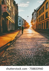 Man tourist walking in sunset street Travel Lifestyle concept vacations cobblestone road Alesund city in Norway