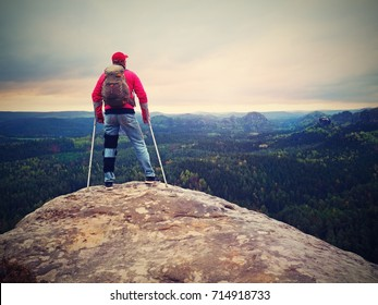 Man tourist wearing a knee brace with adjustable side panels to immobilize and support hurt leg. Man walking against the crutches outdoors on hike trip