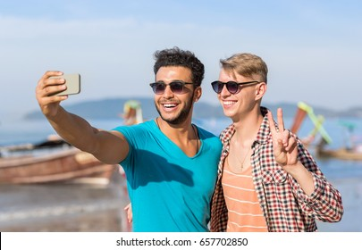 Man Tourists Couple Taking Selfie Photo In Front Of Long Tail Boat On Beach On Cell Smart Phone, Two Young Guys Happy Smiling On Sea Vacation