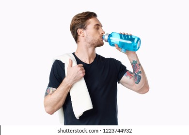 a man with a towel on his shoulder drinks water from a bottle