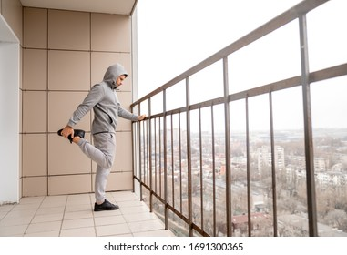 A man in a tracksuit does sports exercises near the balcony on the balcony of an apartment building. Self-isolation and quarantine. Fresh air and physical activity.