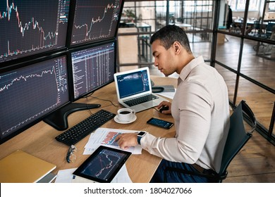Man trader in formalwear sitting at desk in frot of monitors with charts and data at office browsing laptop checking documents analyzing stocks price changes concentrated drinking hot coffee trading