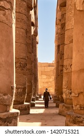 Man in traditional Arab clothes walks among the massive pillars of the Great Hypostyle Hall within the Karnak temple complex (about 1250 BC), Luxor, Egypt