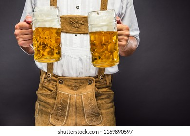 Man in traditional bavarian clothes holding mug of Oktoberfest beer
