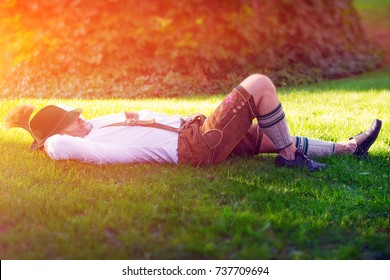 man in traditional bavarian clothes sleeping outside in the grass