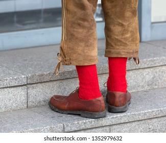Man in traditional Bavarian leather trousers Lederhosen and red socks