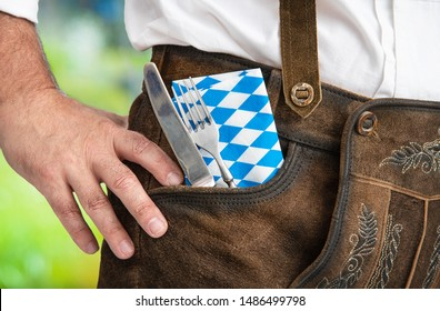 Man in traditional Bavarian Lederhosen with cutlery in his trouser pocket