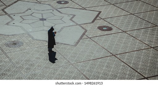 Man in traditional black dress with hood standing in the middle of empty  square with handy in the hand