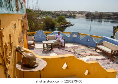 A man in traditional clothes sitting in front of a Nubian-style house, Aswan, South Egypt August 12, 2015,