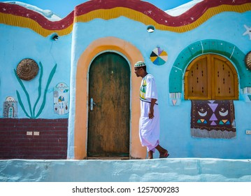 A man in traditional dress next to a traditional Nubian house, Nubia, southern Egypt, August 2015