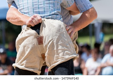 Man with traditional swiss wrestling trousers and shirt in the sawdust