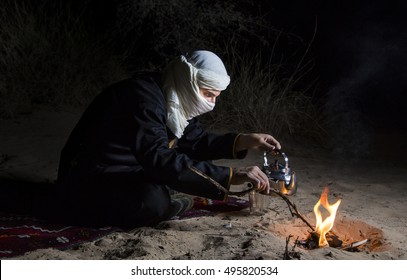 Man in traditional Tuareg outfit in a desert, preparing tea