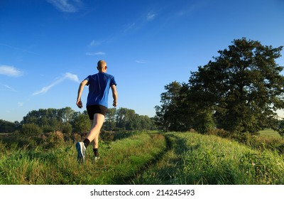 Man trail running in the countryside on a sunny morning.