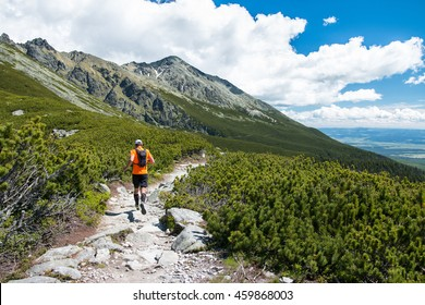 man trail running for fitness on stony path in high mountains with peak view and blue sky