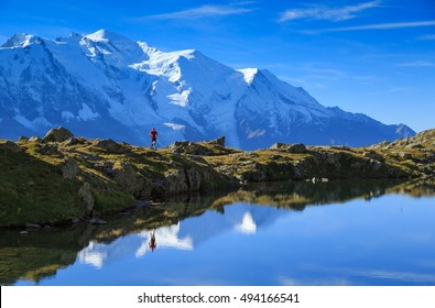 Man trail running at Lac De Cheserys, with the famous Mont Blanc in the background.