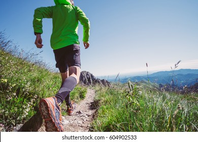 Man trail running on a mountain in summer