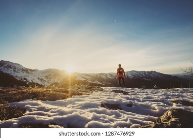 Man trail running in winter on the snow
