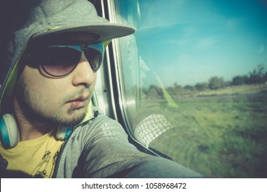 Man in a train carriage. Handsome Young Asian man wearing sunglasses looking through train window and exploring green nature landscape outside. A man sitting in the train and looks out the window.