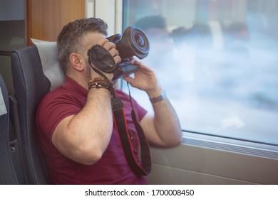 Hombre en el tren tomando fotos desde afuera en una ventana