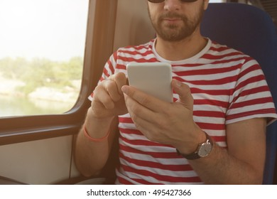 Man in train using cellphone.