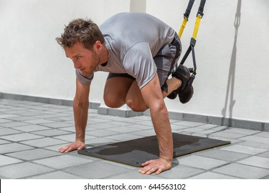 Man training abs core body muscles with suspension fitness straps at gym. Stomach abdominals workout healthy lifestyle sport.
