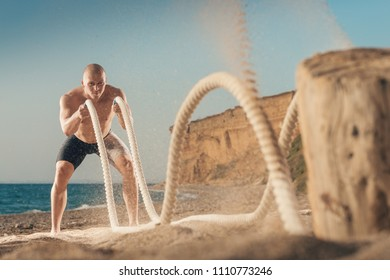 Man training with battle rope on the beach. Athlete doing cross fit workout outdoor. Sport fit exercise.