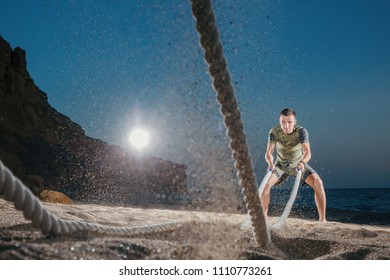 Man training with battle rope on the beach. Athlete doing cross fitness workout outdoor. Sport fit exercise.