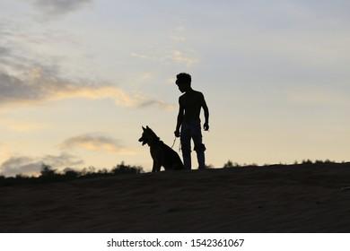 man training his dog at dusk