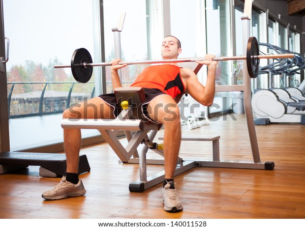 Man training on a bench in a fitness club