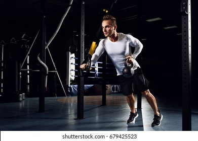 Man training with trx fitness straps and kettlebell in the gym . Crossfit man at the gym doing TRX excersise. Workout on rings.