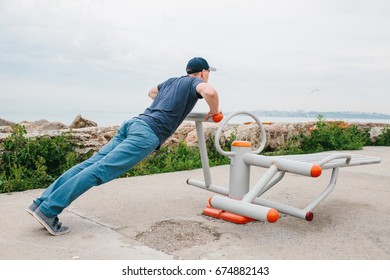 A man trains on sporting equipment in a city in the open air. The concept of a healthy lifestyle and accessibility of sports training for every person. Available sports equipment in a public place.