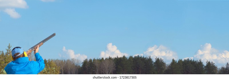 man trains to shoot a double-barreled hunting rifle on a sports stand in a blue sky shooting club, clay pigeon in to the blue sky , copy space