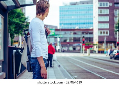man at a tram stop in Amsterdam, young man standing at the bus stop waiting for the tram. Netherlands Amsterdam, traffic