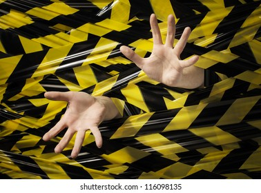 A Man trapped behind yellow and black barrier tape.