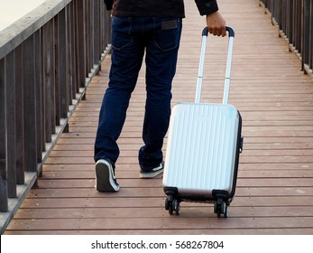 Man with travel suit case on the wooden bridge background