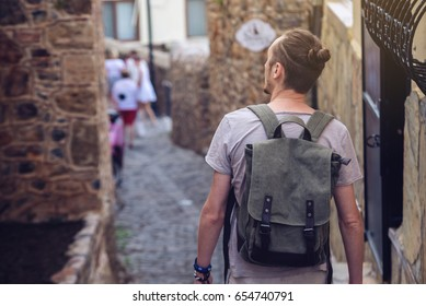 Man traveler with backpack explore the village walking on the old streets and explore the castles and fortresses. The concept of travel is discovering new places