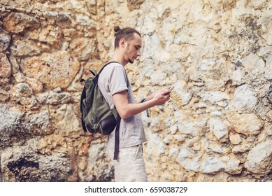 Man traveler with backpack looking at his smartphone on the background of a stone wall. The concept of connection and communication in the journey.