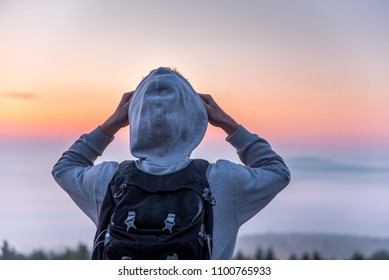 A man traveler with a backpack on his back looking at the sunrise in the morning mist on a hill.