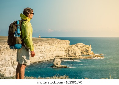 Man Traveler with backpack relaxing outdoor Sea and Rocks coastal on background Freedom Lifestyle concept