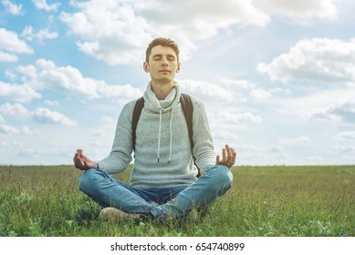 Man traveler with backpack sits on meadow with green grass under blue sky with clouds in the Lotus position. Meditating in complete tranquility and freedom