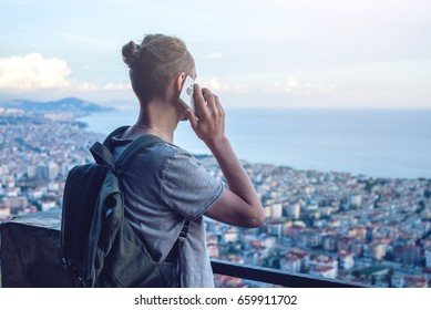 Man traveler with backpack talking on the phone on background of the city. The concept of connection and communication in the journey, roaming.