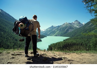 Man Traveler with big backpack mountaineering Travel Lifestyle concept lake and mountains on background Summer extreme vacations outdoor. Altai mountains. Lake kucherlinskoe. Siberia. Russia.