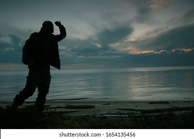 man traveler by the lake, silhouette of a man on a campaign, activity