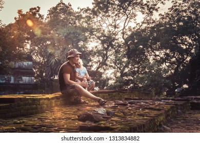 Man traveler with child daughter resting together on ruins at sunset during vacation concept travelling lifestyle