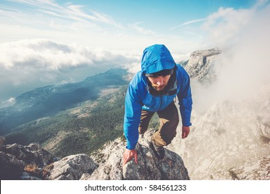 Man Traveler climbing on mountain summit over clouds Travel Lifestyle success concept adventure active vacations outdoor extreme sport