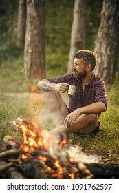 Man traveler drink tea at campfire flame. Camping, hiking, lifestyle. Summer vacation concept. Hipster hiker with mug relax at bonfire in forest. Travel, traveling, wanderlust.