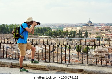 man traveler in a hat with a backpack and camera admiring the view of the city of Toledo from the observation deck
