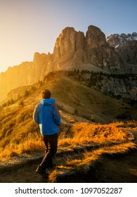 Man traveler hiking alone in breathtaking landscape of Dolomites Mounatins at sunrise in summer in Italy. Travel Lifestyle wanderlust adventure concept. Outdoor wilderness vacations.