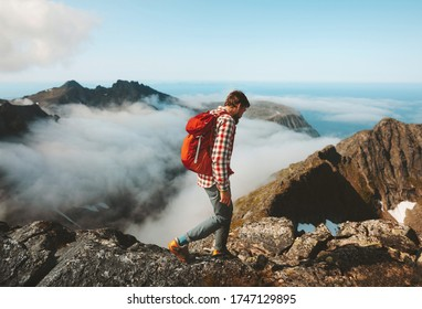 Man traveler hiking with backpack above clouds travel outdoor in mountains adventure vacation active healthy lifestyle extreme sports summer activity in Norway